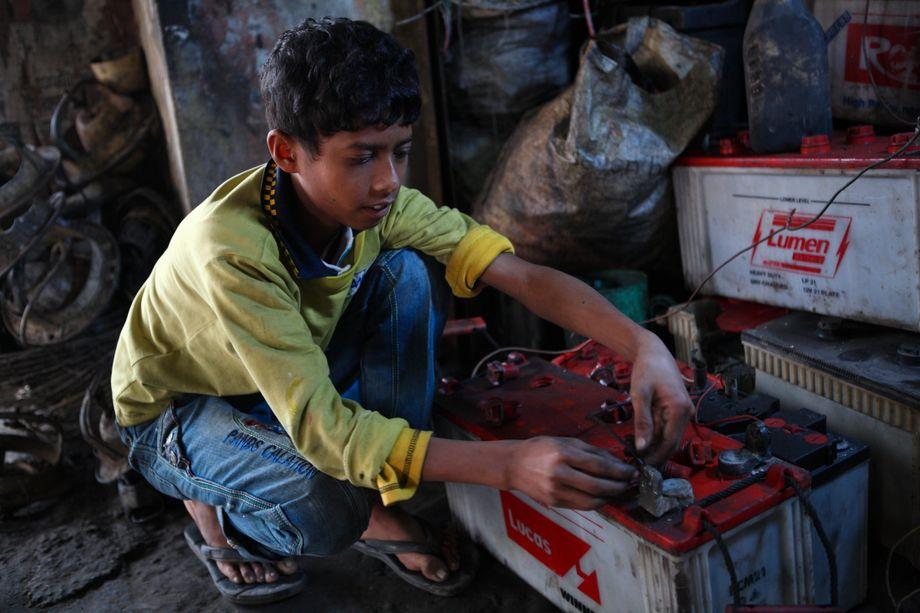 Der zehnjährige Al Amin arbeitet in einer Werkstatt in Bangladesch, in der er ohne Schutzkleidung Batterien repariert