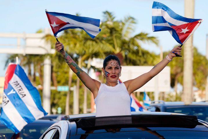 Eine Demonstrantin schwenkt kubanische Flaggen während einer Autoparade