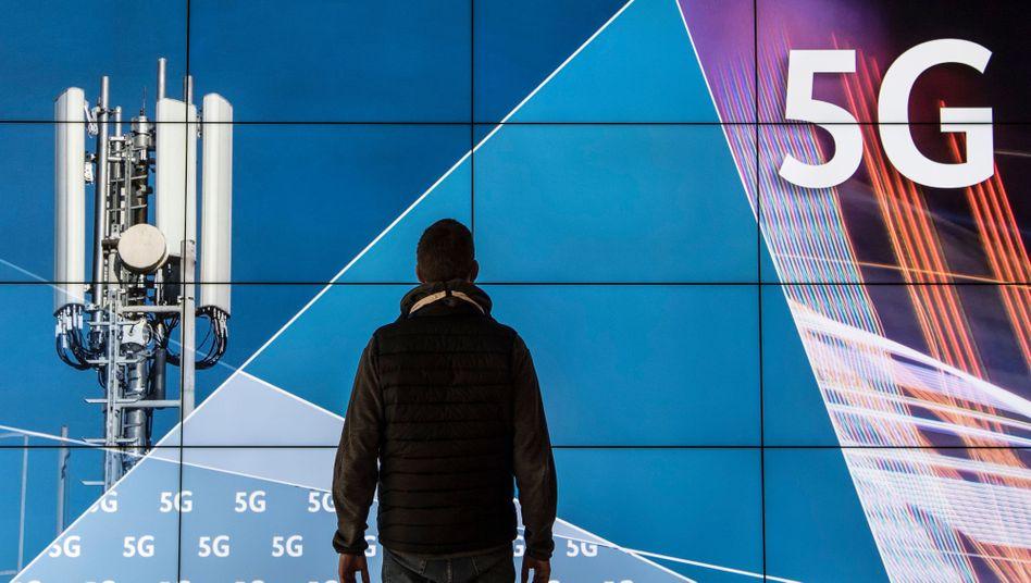 """Ein Mann steht im Gebäude der Bundesnetzagentur vor einer Leinwand mit der Aufschrift """"5G"""""""