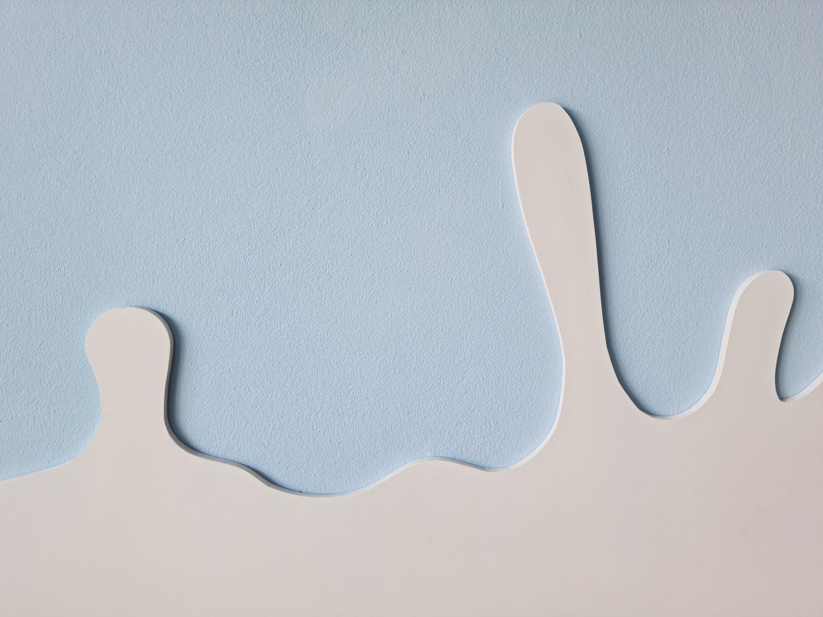Shape of milk splashing on the blue pastel background