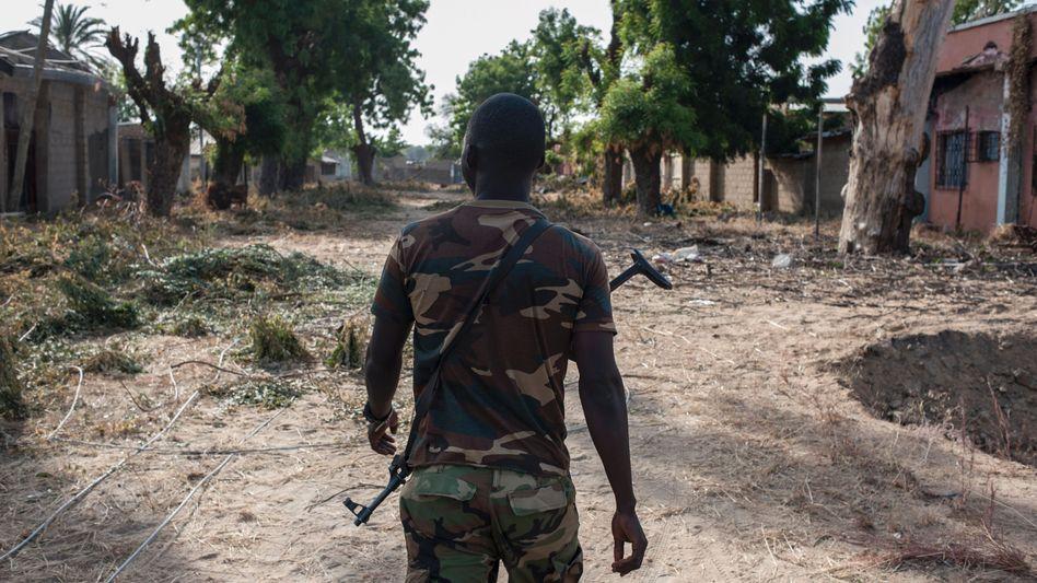 Nigerianischer Soldat patrouilliert durch das von Boko-Haram-Milizen zerstörte Bama (Archiv)
