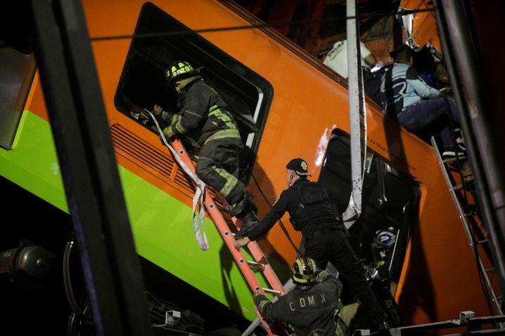 Feuerwehrleute bahnen sich einen Weg durch die Trümmer