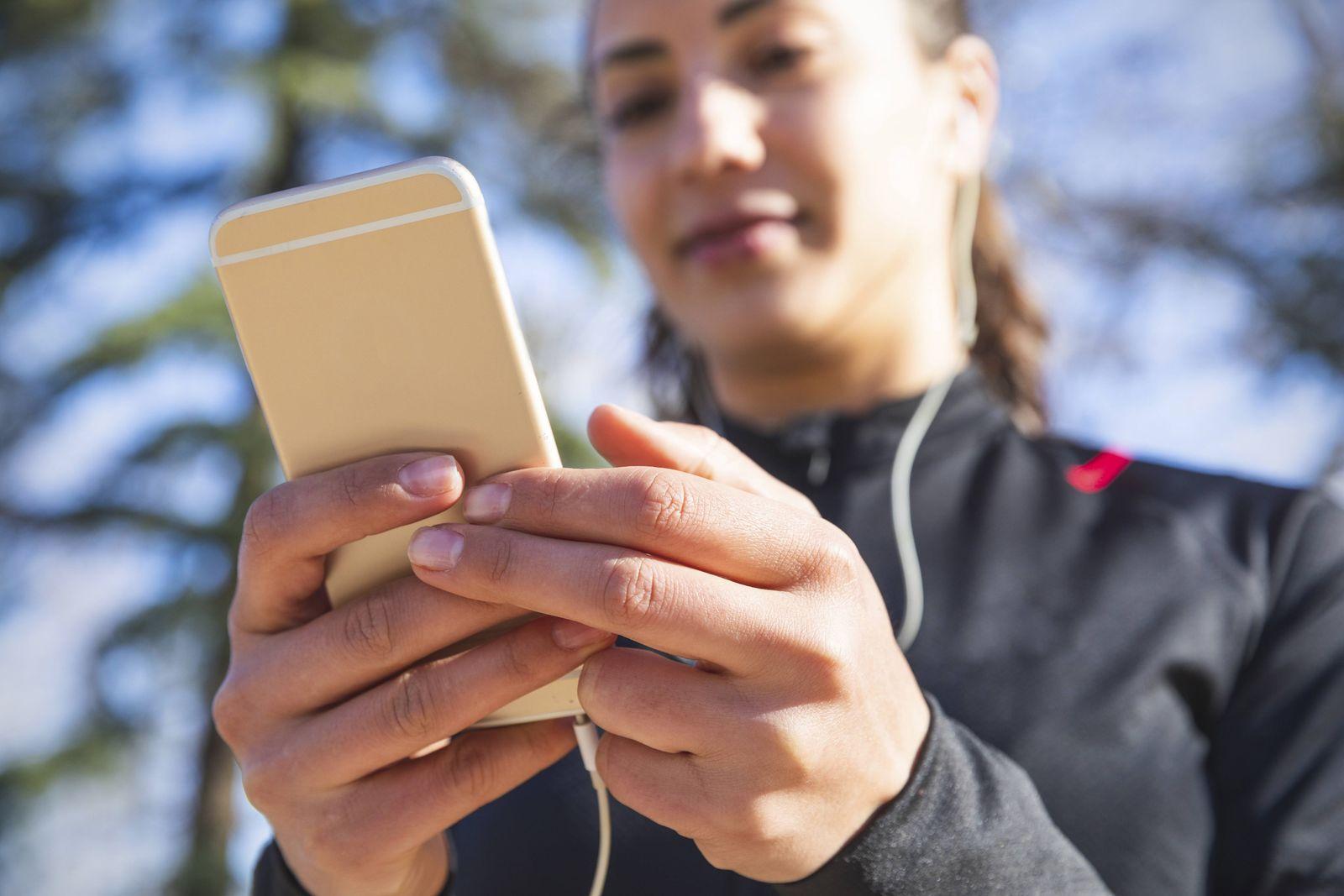 EINMALIGE VERWENDUNG Smartphone/ Frau/ Herbst