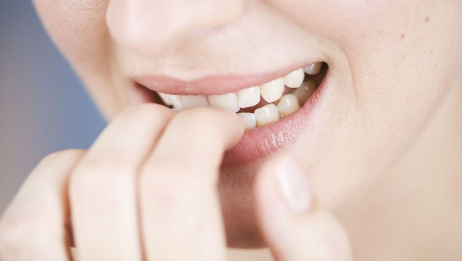 Frau kaut Nägel: Eine einfache Therapie kann beim Aufhören helfen