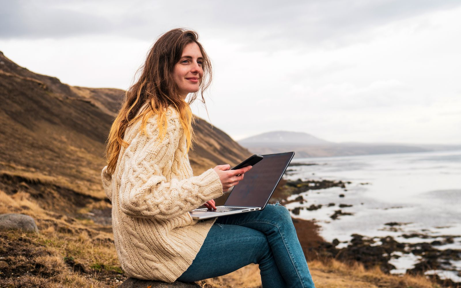 Iceland, woman using laptop and cell phone at the coast