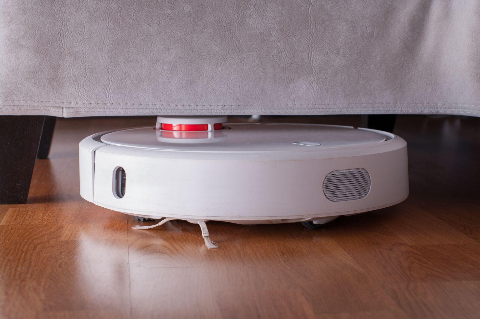 Close-Up Of Robotic Vacuum Cleaner On Hardwood Floor