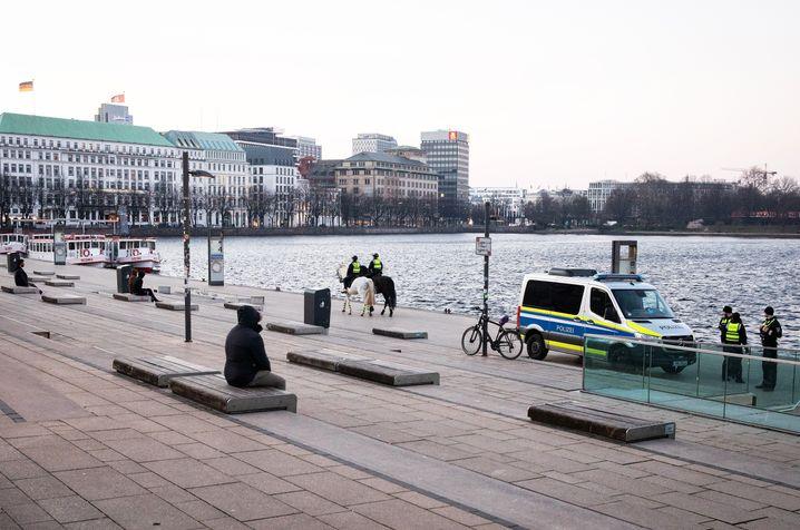 Polizei und wenige Passanten am Hamburger Jungfernstieg: Die Hansestadt hat gerechnet auf 100.000 Einwohner die meisten Infektionsfälle