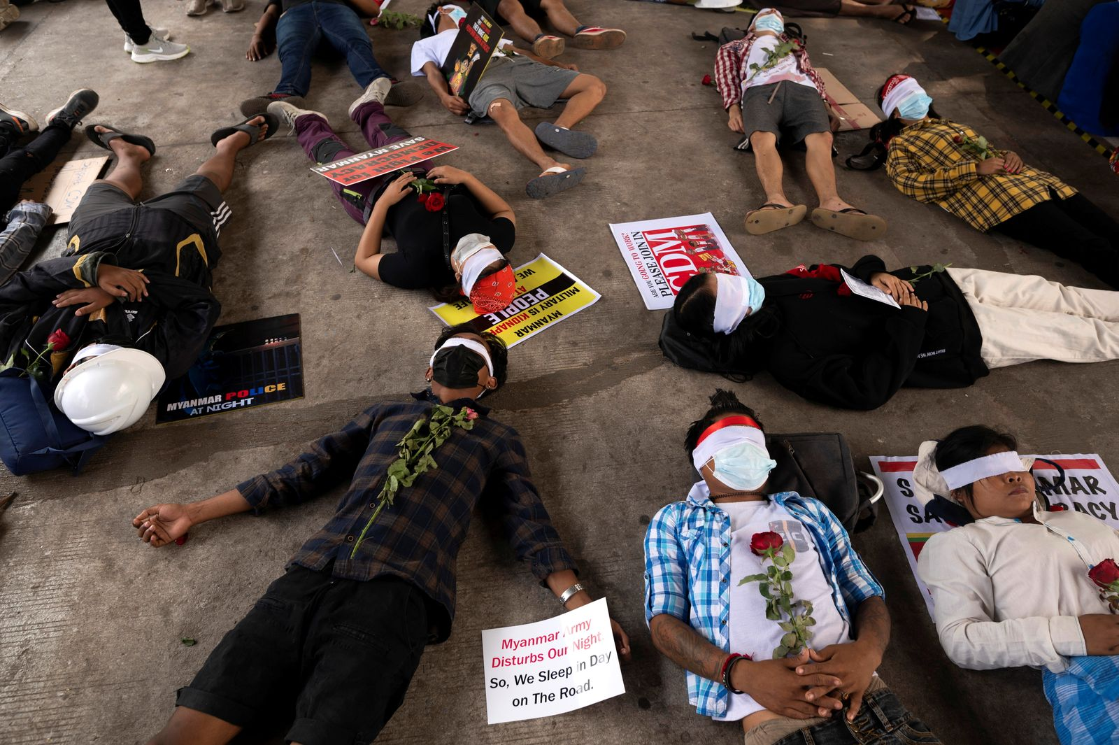 People lie down on the floor as they take part in a protest against the military coup in Yangon, Myanmar
