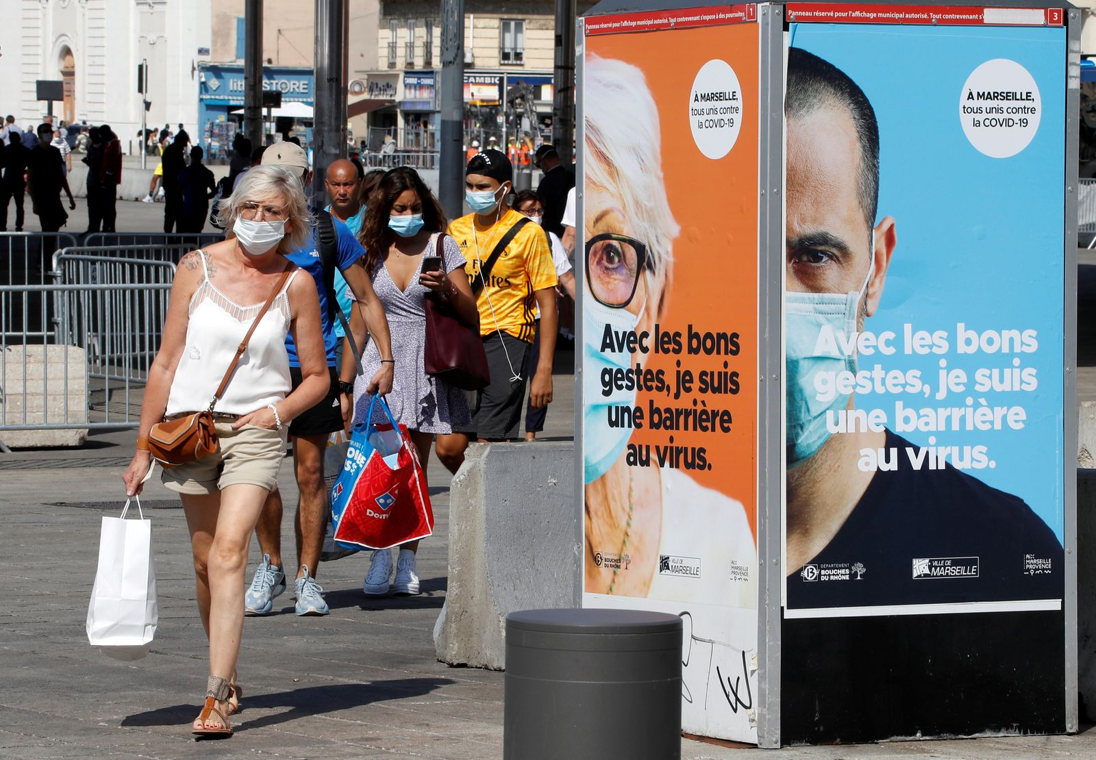 FILE PHOTO: People wearing protective face masks walk near the Old Port in Marseille