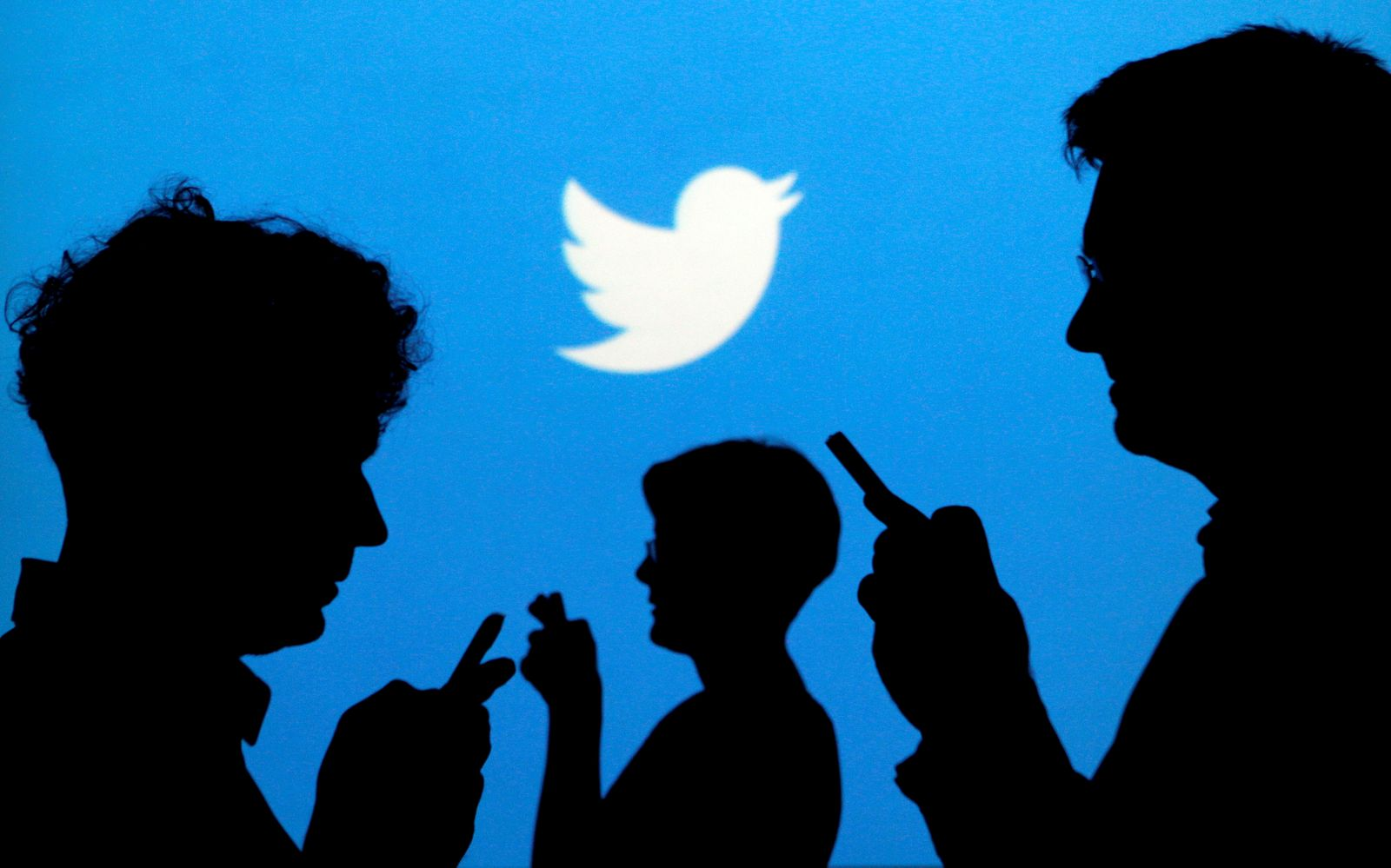 FILE PHOTO: Smartphone users are silhouetted against a backdrop projected with the Twitter logo