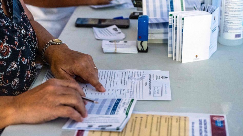 Eine Frau in einem Impfzentrum in Frankreich prüft die Kontaktdaten von Impfwilligen (Symboldbild)