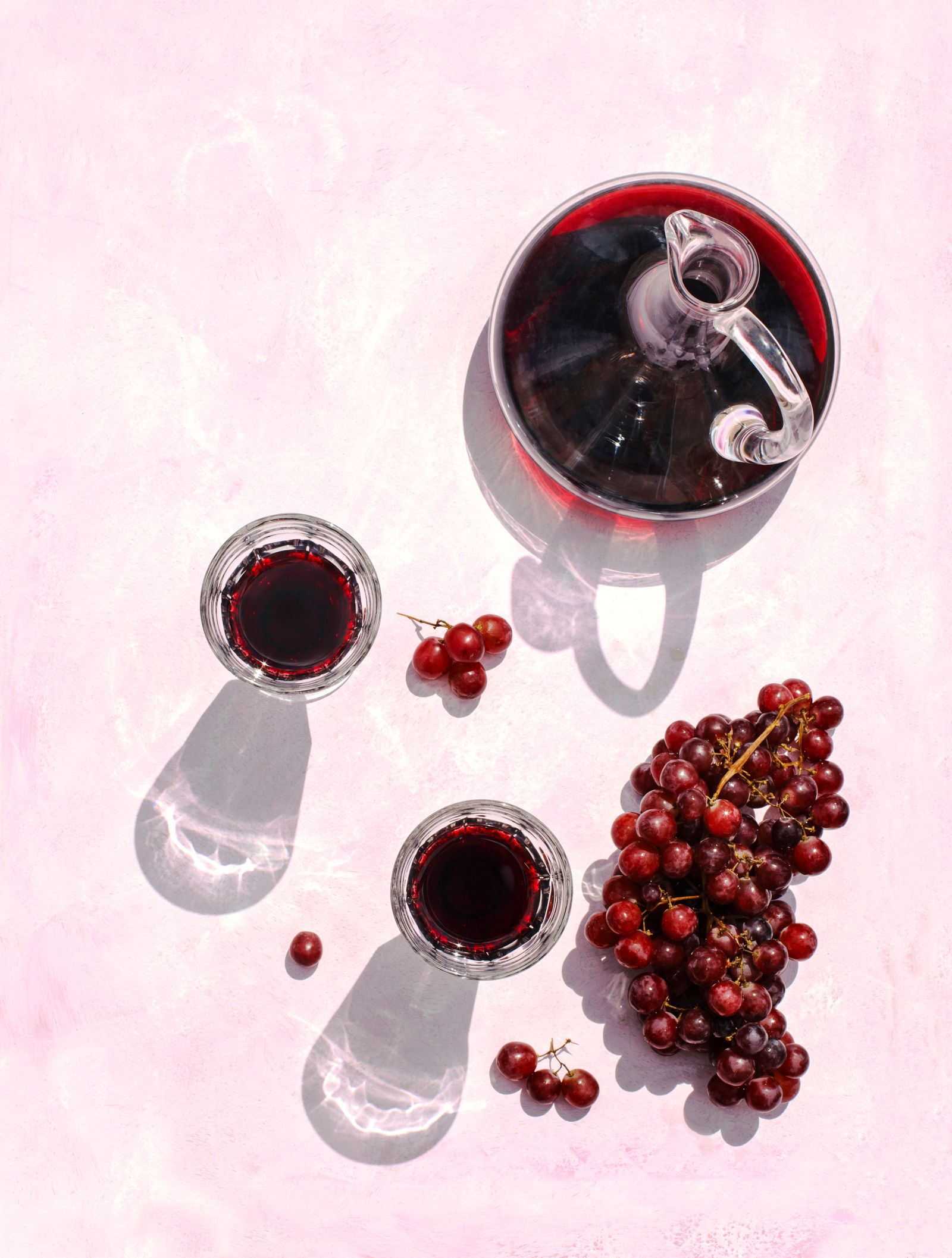Glasses of red wine, decanter and grape on pink background, top view