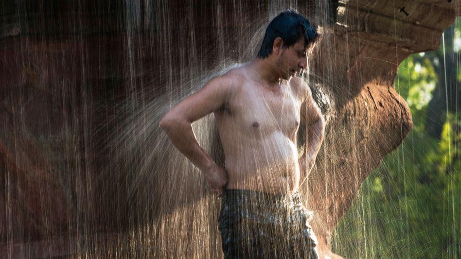 Ein Inder nimmt am Triumphbogen in Neu-Delhi eine Dusche