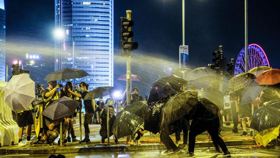 Die Polizei in Hongkong spritzte Wasser auf Demonstranten, die sich außerhalb der Zentralregierung versammeln.