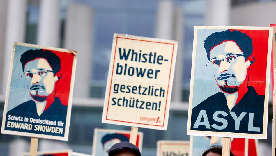 Democracy activists in Berlin hold signs demanding asylumn for whistleblower Edward Snowden in Germany.