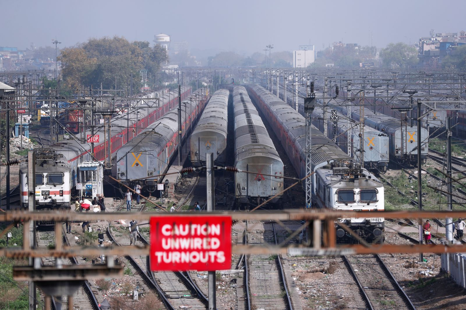 People walk next to parked trains during lockdown by the authorities to limit the spreading of coronavirus disease (COVID-19), in New Delhi