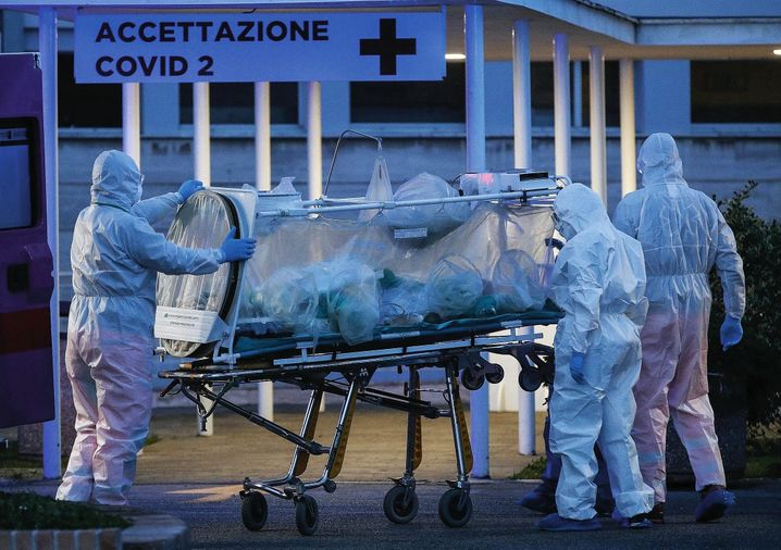 Medical workers transport a patient with novel coronavirus in Rome: There are fears in Germany the disease could kill thousands of people here.