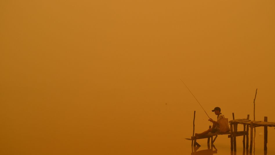 A man fishing in the haze of severe forest fires in Indonesia this autumn.