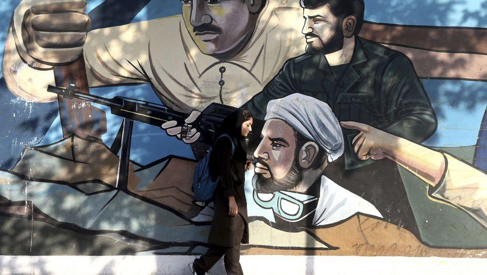 An Iranian woman walks past a mural in Tehran.