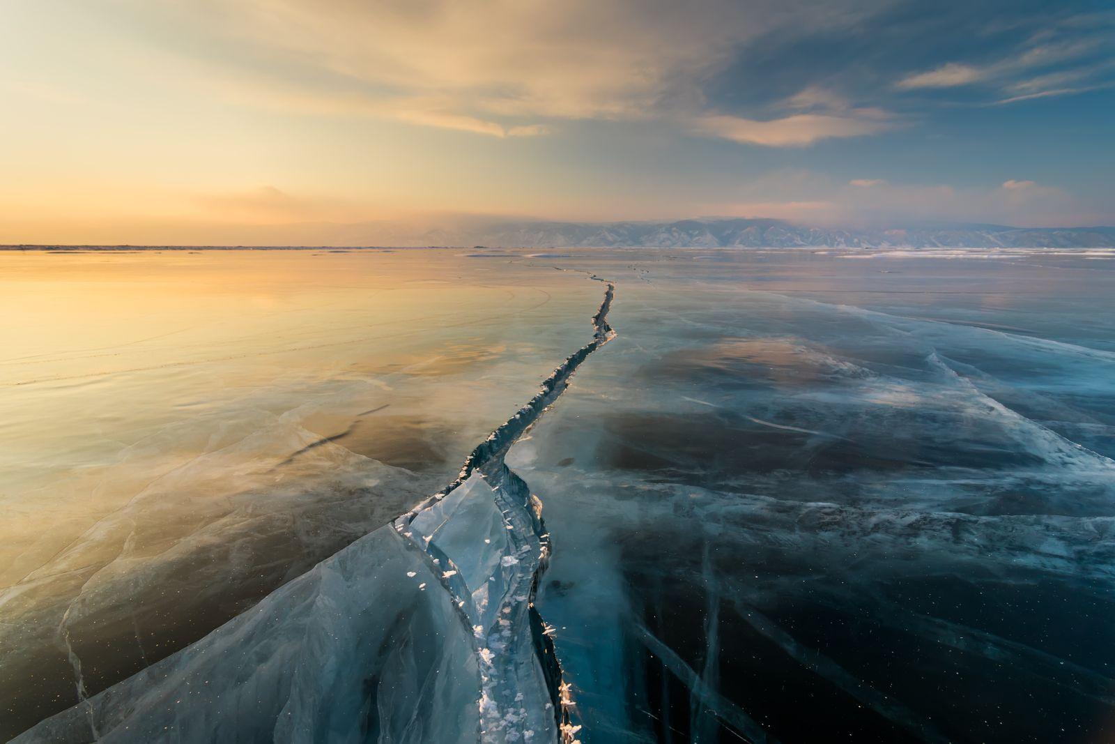 Sunset on the ice with cracks. Baikal, winter