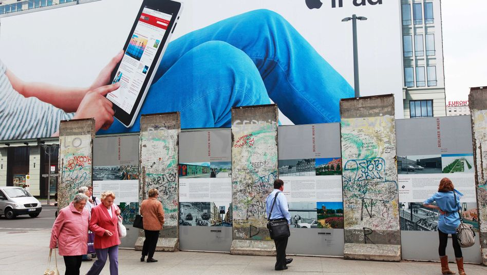 People walk past and look at a section of the fallen Berlin Wall in front of a giant billboard featuring Apple's new iPad.