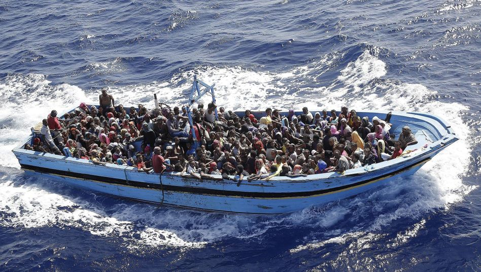 A boat packed with migrants after being discovered by the Italian Navy.