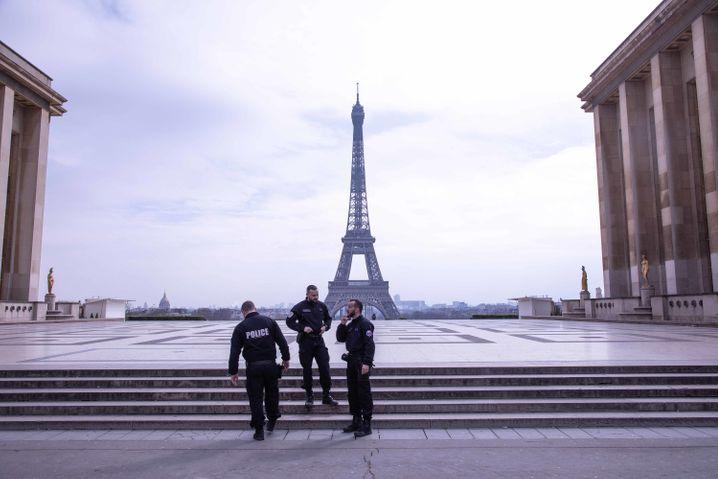 Strenge Regeln, harte Strafen, leere Straßen: Französische Polizisten auf der Trocadero-Terasse vor dem Eifelturm