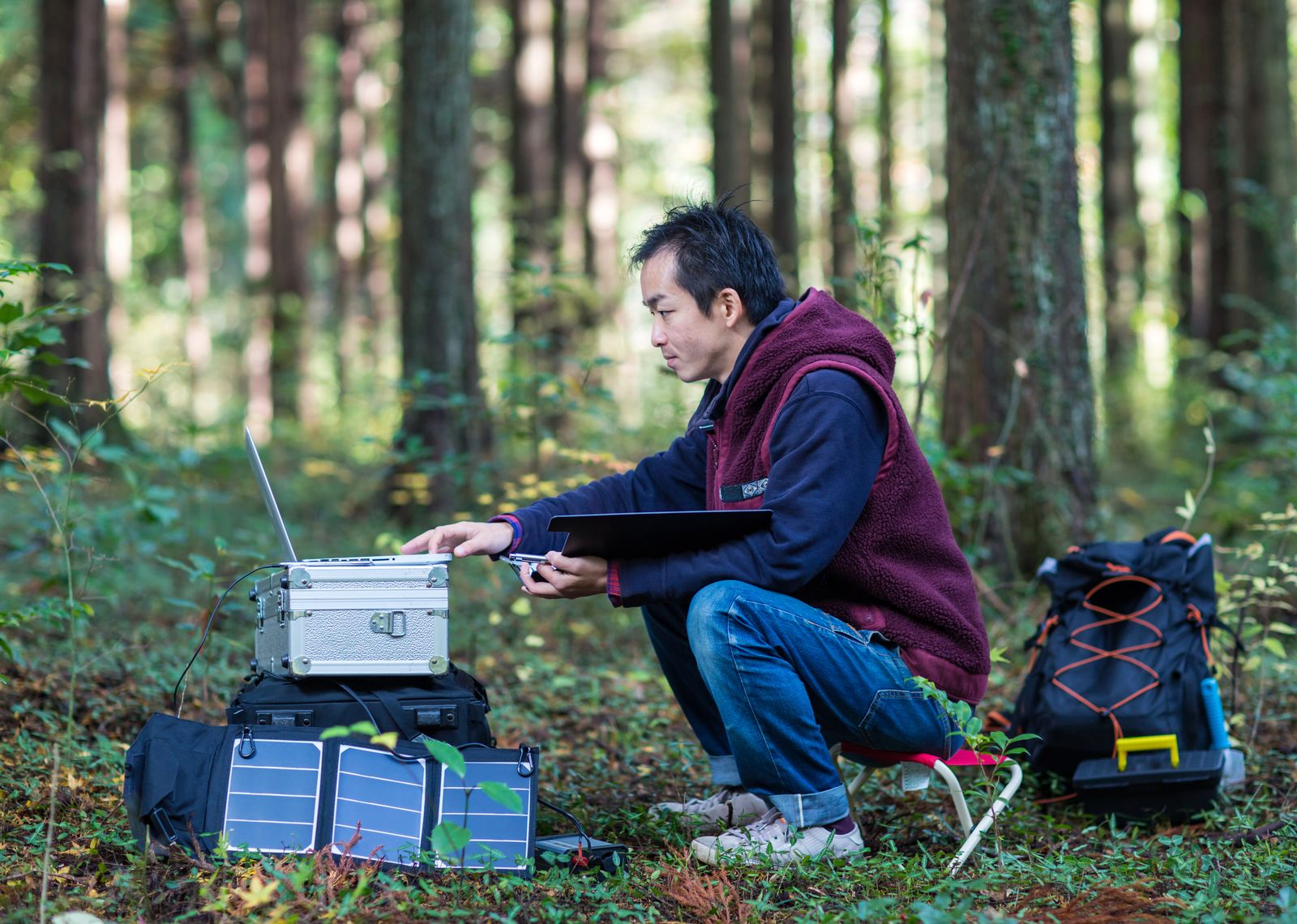 Environmentalist inputting data at a solar powered field station