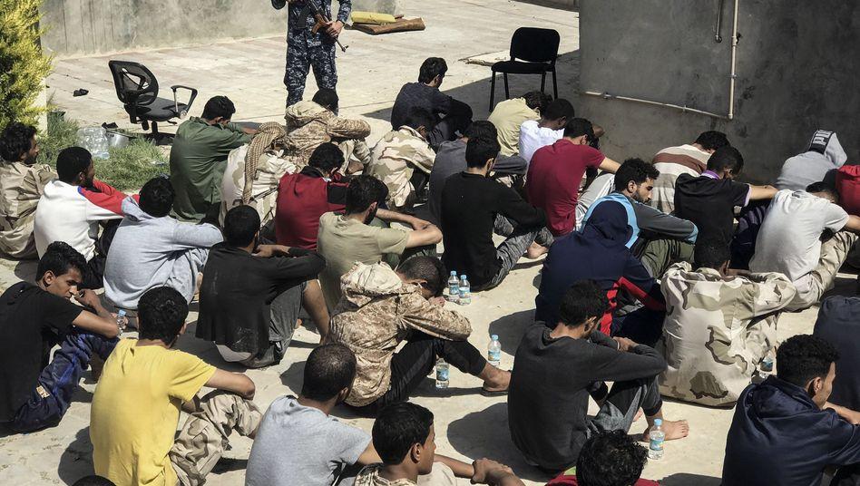Libysche Kämpfer, die der selbsternannten Libyschen Nationalarmee (LNA) unter der Führung des libyschen Generals Haftar angehören, sitzen unter Bewachung in einer Haftanstalt