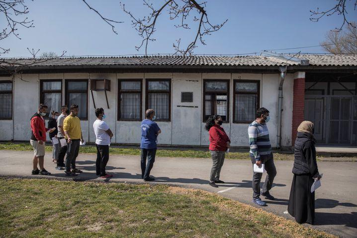 Warten auf Schutz: Migranten und Migrantinnen vor einem Impfzentrum in Belgrad