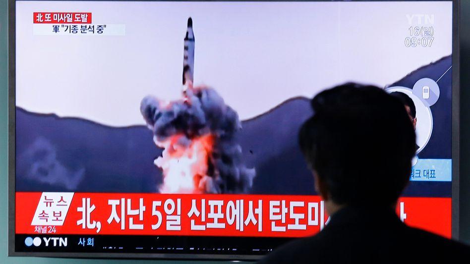 Ein Mann sieht am 16.04.2017 am Bahnhof in Seoul (Südkorea) auf einem TV-Gerät eine Archivfilmaufnahme von einer nordkoreanischen Rakete