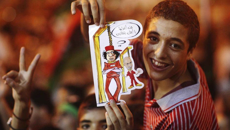 A boy holds a drawing depicting Moammar Gadhafi and his son Seif al-Islam being hanged during celebrations of the capture in Tripoli.