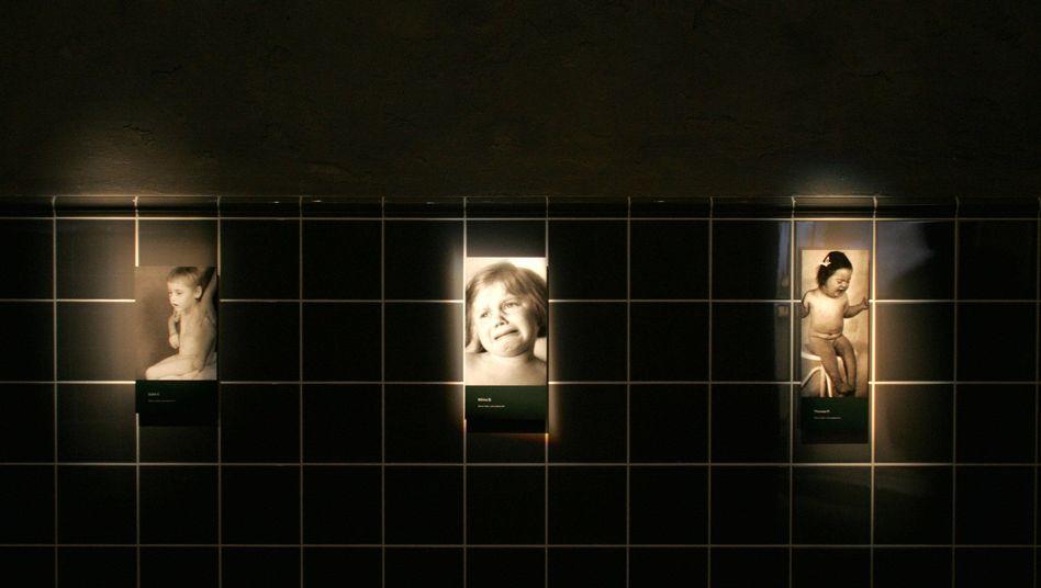 """Fotografien von Kindern haengen am Mittwoch (11.10.06) in der Ausstellung """"Toedliche Medizin. Rassenwahn im Nationalsozialismus"""" im Deutschen Hygiene-Museum in Dresden auf einer Fliesenwand."""