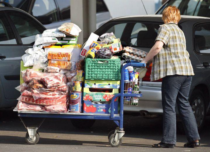 Frau mit voll beladenem Einkaufswagen