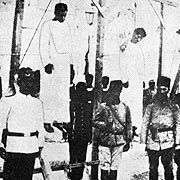 Picture circa 1915 of Turkish soldiers standing next to the hanged bodies of Armenians.