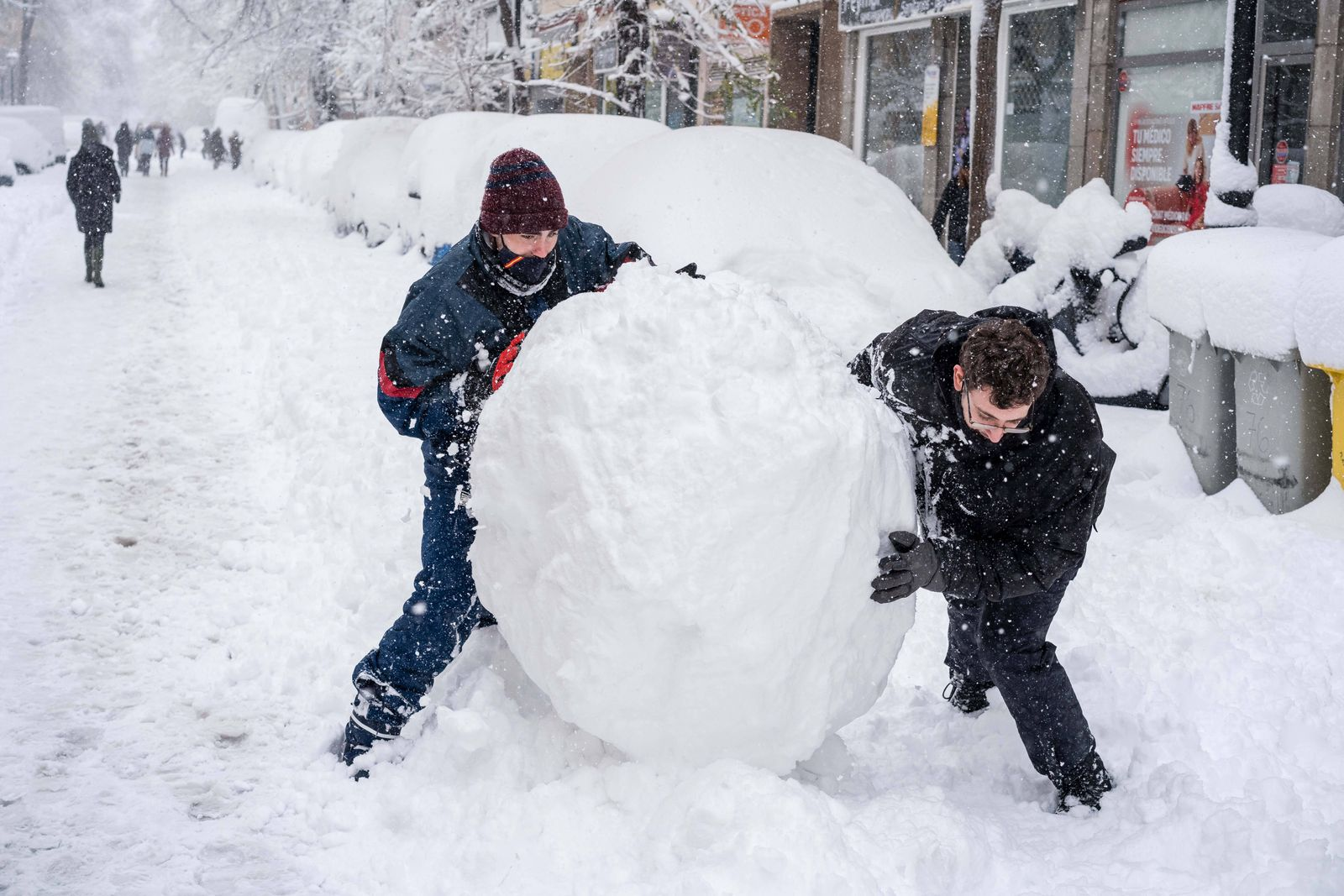 January 9, 2021, Madrid, Spain: Youth seen pushing a snowball in the streets of the Chamberi neighborhood, central Madr