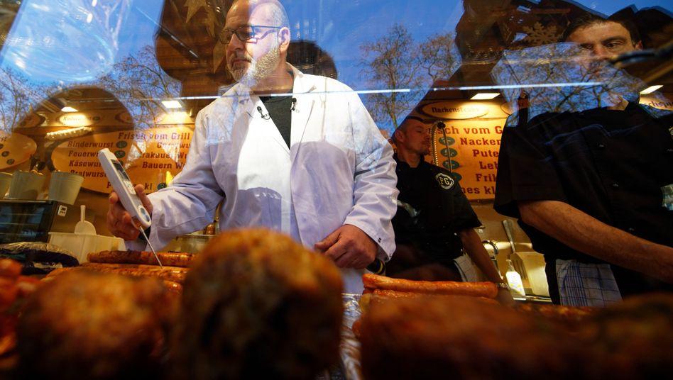 Ein Lebensmittelkontrolleur prüft im Auftrag der Stadt Köln einen Stand auf dem Weihnachtsmarkt