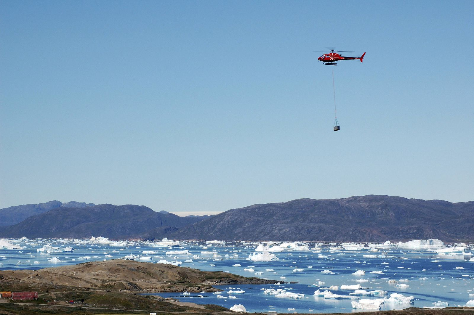 Helicopter delivering Research material from uranium mining project based in the mountains Narsaq