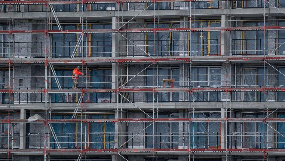 Ein Arbeiter geht in Hamburg auf einer Baustelle über ein Gerüst