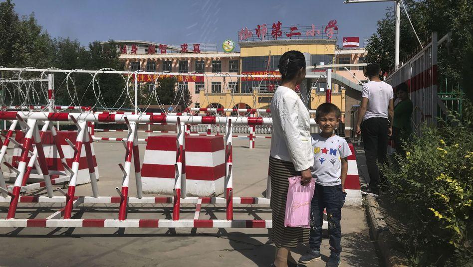 Uiguren vor einer umzäunten Schule in der Provinz Xinjiang in China (Archiv)