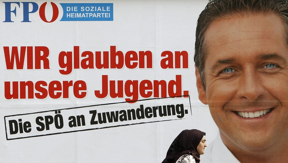 A woman in a headscarf walks past a campaign poster for the Freedom Party of Austria depicting party leader Heinz-Christian Strache.