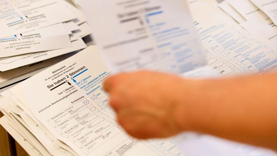 Wahlhelfer sortieren und zählen Stimmzettel in einem Wahllokal
