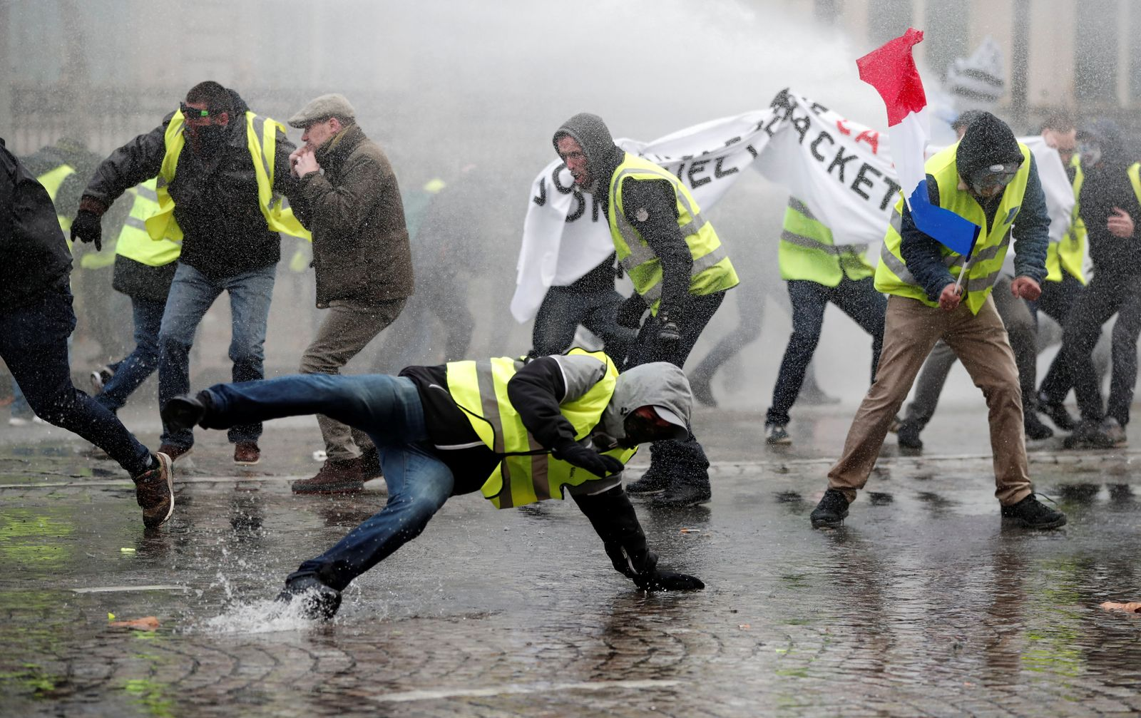Protesters wearing yellow vest, a symbol of a French drivers' protest against higher fuel prices, stand up in front of a police water canon during clashes on the Champs-Elysees in Paris
