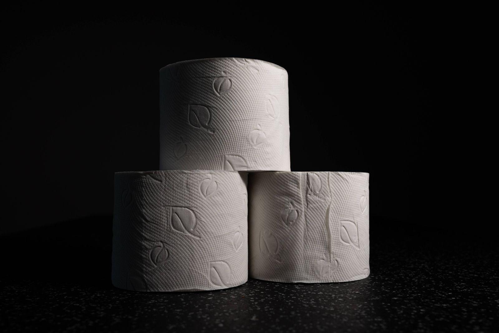 Klopapier, Toilettenpapier Symbolbild, 3 Rollen Toilettenpapier auf dunklem Hintergrund. *** Toilet paper, toilet paper