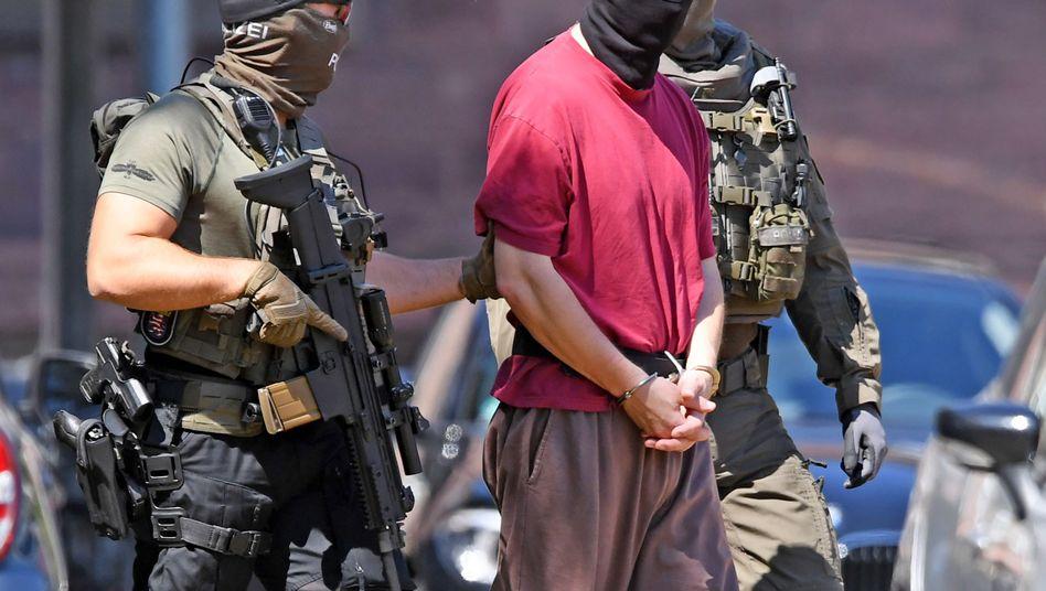 Polizisten führen den Tatverdächtigen nach einem Haftprüfungstermin ab.