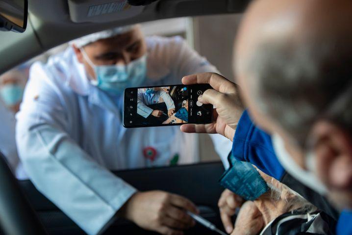 Ein Mann fotografiert, wie seiner Mutter im Auto eine Covid-19-Impfung verabreicht wird
