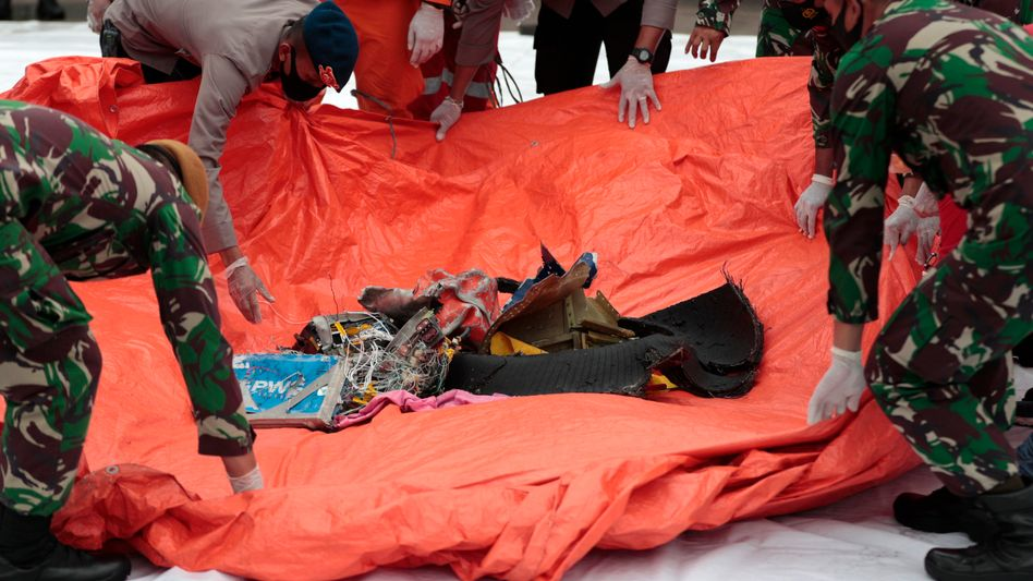 Einsatzkräfte sammeln Fundstücke, die aus der vor Java ins Meer gestürzten Boeing stammen sollen