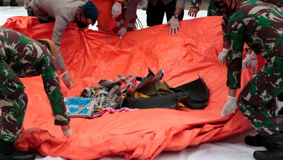 Soldaten und Polizisten breiten gefundene Flugzeugteile aus