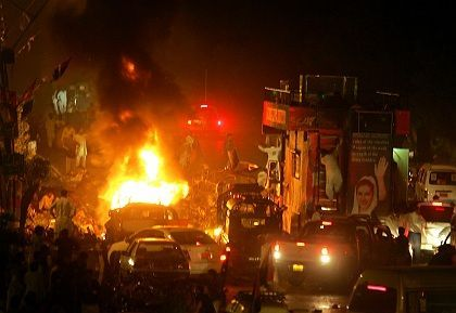 A fire erupts from a car in front of an armored vehicle carrying former Pakistani Prime Minister Benazir Bhutto following a bombing on the convoy in Karachi. Two bomb explosions killed at least 134 people and injured over 400 injured in two bomb explosions.