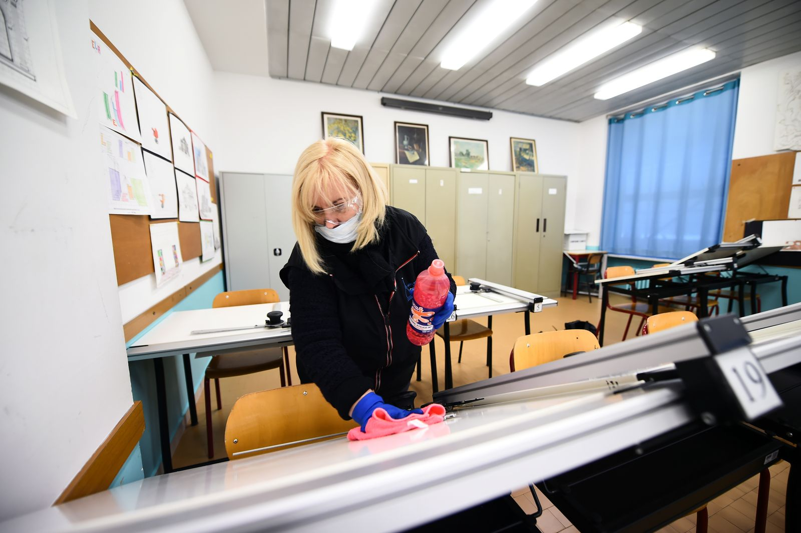 A cleaner sanitises a classroom at the Piero Gobetti high school in Turin